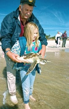 Man and young girl holding turtle