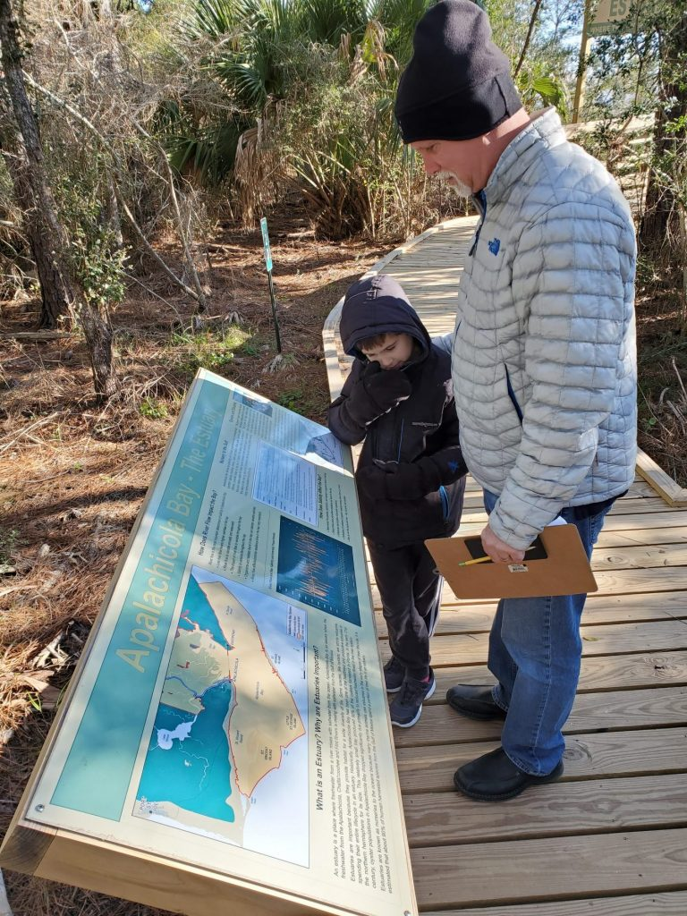 Parent and child study a Watershed Walk display